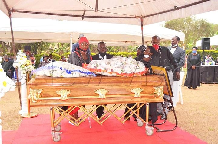 Ruth Ddungu's children laying a wreath on their mother's casket. Photos by Mathias Mazinga