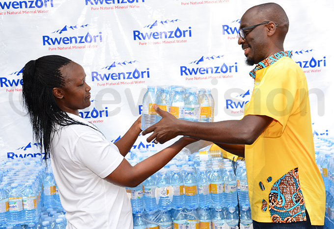 wenzori aters lavia abaasa left presents a carton of water to s artin sebuliba hoto by ichael subuga