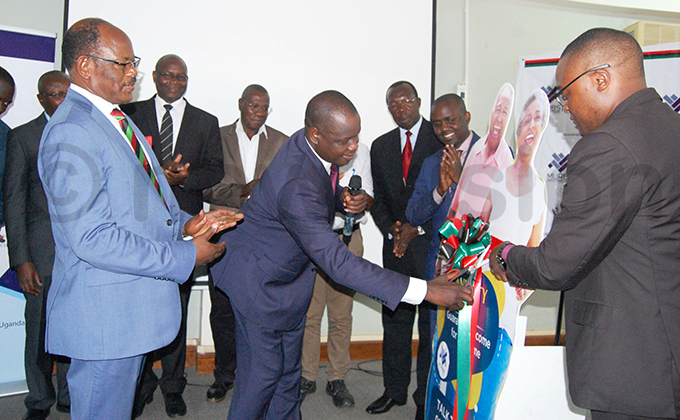 akerere niversity ice hancellor arnabas awangwe left and niversity ouncil vice president an idega cutting tape with other members at the launch of the performance report of akerere niversity etirement enefit cheme  for the finance year 201819 hoto by ylvia atushabe