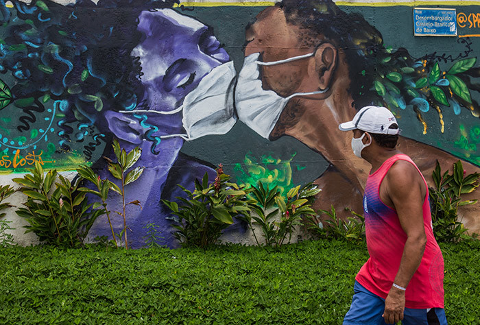 man wearing a face mask walks past a graffiti by artist arcos osta or praycabuloso at the entrance of the olar de nhao favela in alvador on pril 15 2020  razil has registered 1532 deaths from the new coronavirus so far hoto by