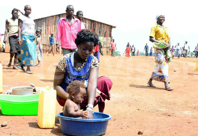 woman bathing her child at the settlementreditddie sejjoba