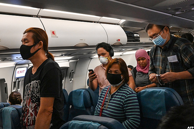 assengers wearing masks arrive on a flight from taly at uarulhos nternational irport in uarulhos ao aulo razil
