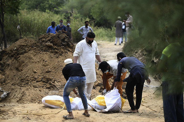 elatives prepare the dead body of a woman who died from the 19 coronavirus disease before her burial at a graveyard in ew elhi on pril 16 2020 hoto by ajjad