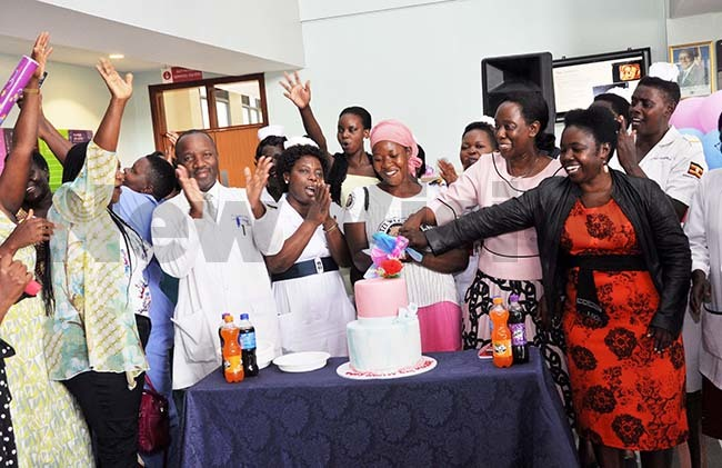 r velyn abunya second right the director ulago pecialized women and eonatal hospital cuts a cake with patients and doctors during the omens day medical camp to celebrate orld omens day at ulago pecialized women and eonatal hospital on 8th arch 2020 hoto by uliet asirye