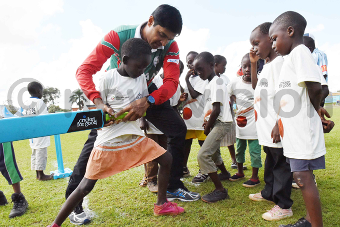 mans jay alcheta helps a young girl with her batting hoto by palanyi sentongo