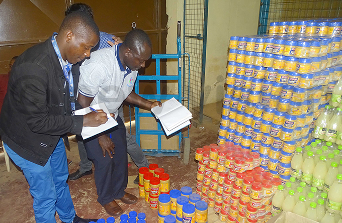 surveillance officers dgar twongire and amuel deke seizing some of the products hoto by amadhan bbey