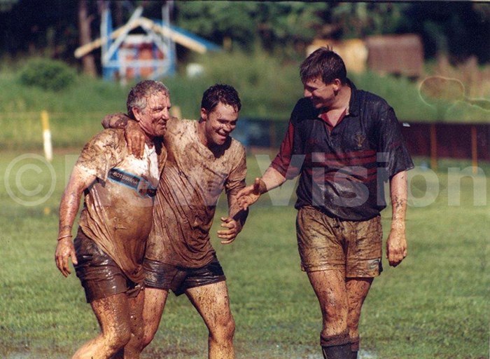 2002 otswana rugby team coach artin olley left walks off with some of his players after testing the muddy yadondo ugby ground ahead of their clash against the ganda rugby side