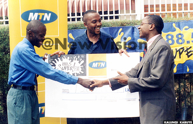 hillip esiimire m and eter ematimba hand over a cheque to a winner in a joint  and uper  promotion