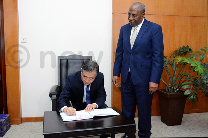 ang signs the visitors book as uganda looks on hoto by iriam amutebi