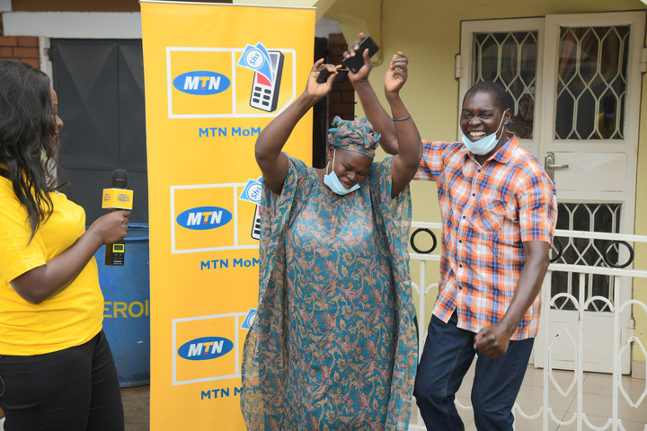Kwanya and his wife jubilateafter receiveing their money on their phones.
