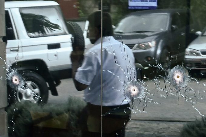 man walks past bullet marks on a glass outside the usit2 hotel complex  hoto