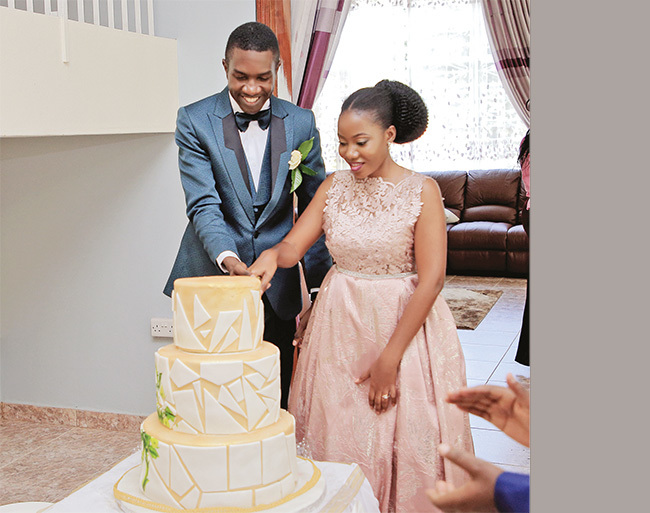 he aziimbas cutting a cake after their wedding lunch at the rchbishops alace in amirembe
