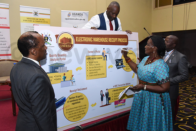 chairman atrick itature minister of trade industry and cooperatives melia yambadde and the state minister for cooperatives rederick gobi ume unveiling the electronic warehouse receipt system during the conference hoto by palanyi sentongo