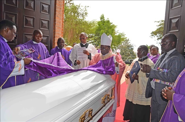 rchbishop wanga and other atholic clerics placing a purple cloth on the casket