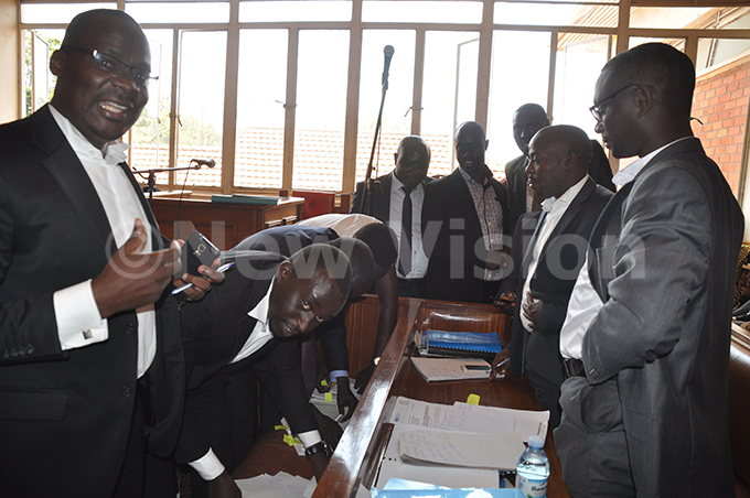 awanda counsel wen urangira and his collegueas prepare to serve artials lead counsel ichard webembezi as ndrew artial standing behind and others look on