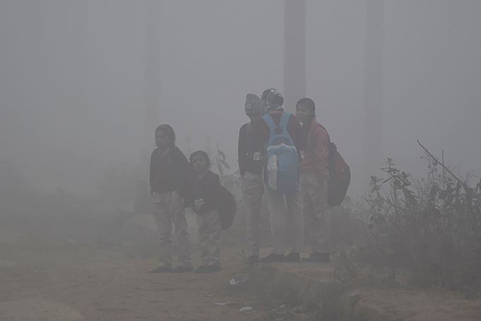 hildren stand on a roadside as they wait for their ride to school amidst heavy fog in aridabad  hoto