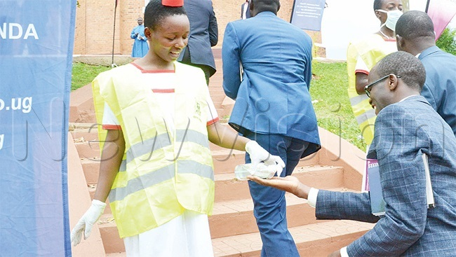 health official sanitising hands of guests who attended the consecration of rchbishop tephen aziimba at amirembe athedral early this year year 19 has made such personal hygiene practices popular