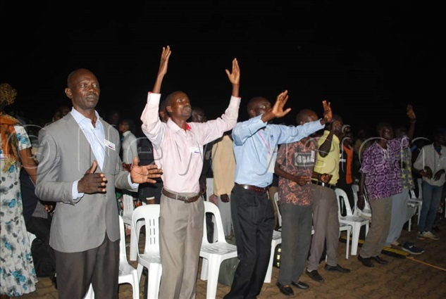 eople in the congregation lifting up holy hands as they worship