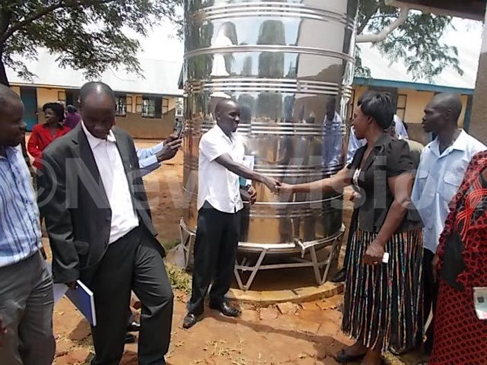 rogram officer uild frica ohn yanu handing over the water harvest tank to the  argaret azikonya at oru rimary school  hoto by awrence kwakol