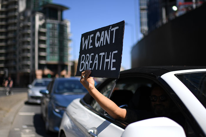sign displaying the message e ant reathe is held out of a car window as demonstrators make their way towards the  mbassy in central ondon on ay 31 2020 to protest the death of eorge loyd hoto by