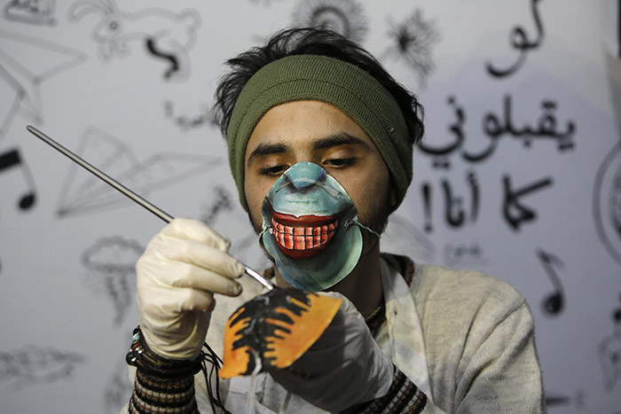 alestinian artist orgham rakeh paints an 95 protective mask for a project raising awareness about the 19 coronavirus pandemic in aza ity on arch 24 2020 hoto by