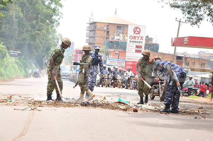 ecurity personnel remove debris from the road that the rioting students threw on 23102019