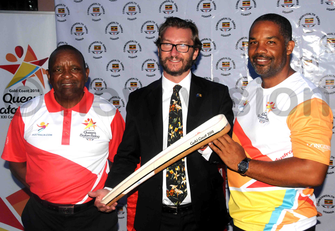 outh frican official am ideon  and the acting ustralian envoy to ganda eremy reen and  president illiam lick pose with the baton hoto by ilvano ibuuka