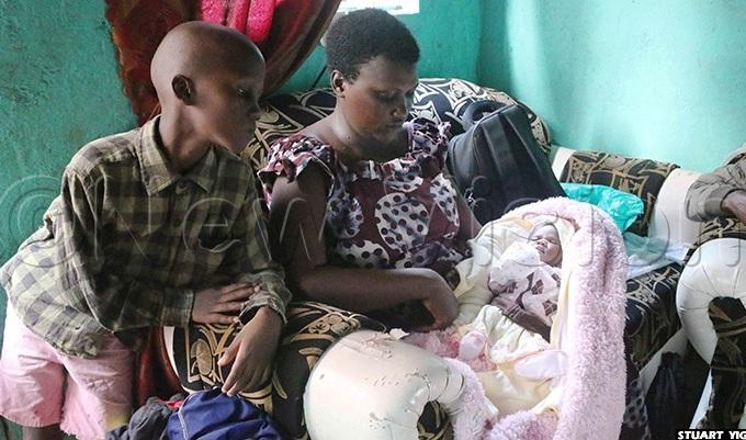 valyne yarisiima carrying her baby as her fiveyearold son hadrack utabaazi looks on