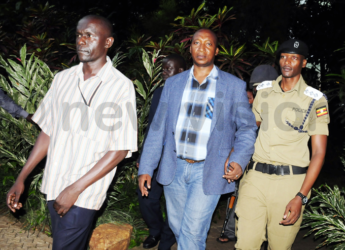 abafunzaki is escorted to a waiting olice car after he was netted at erena otel hoto by ddie sejjoba