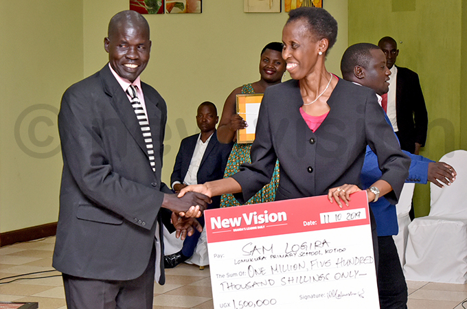 am ogira receives his award from onica hibita the chairperson oard of irectors ision roup hoto by iriam amutebi