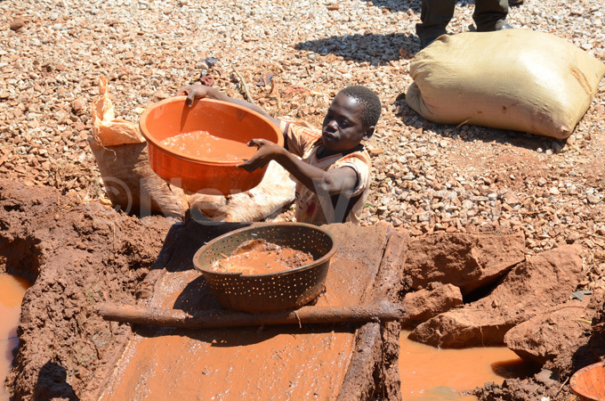 boy trying to extract gold from a blend of crushed ore mud water and mercury at udde in ugiri district