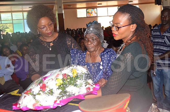he mother of the late t ol harles assaw damulira ary heresa alubega centre lays a wreath on the casket
