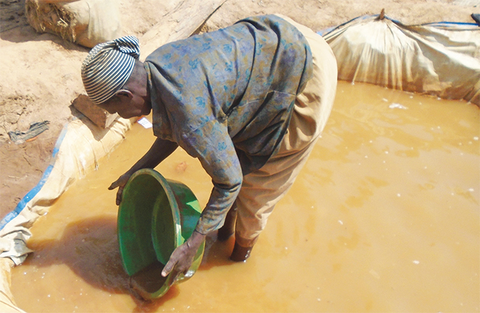 woman sieving dirt to get gold in amayingo district hotos by inah amengo