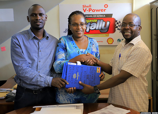 oseph wangla  hands over office files to eila ayanga as assistant secretary rnest iwa looks on