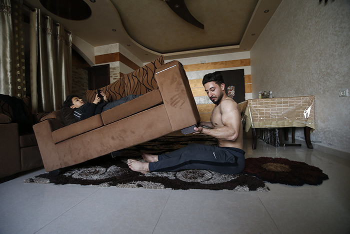 alestinian fitness trainer and bodybuilder hmed awi uses alternative tools as a weight as he trains at his home in aza ity on pril 1 2020 during the coronavirus 19 pandemic hoto by ohammed