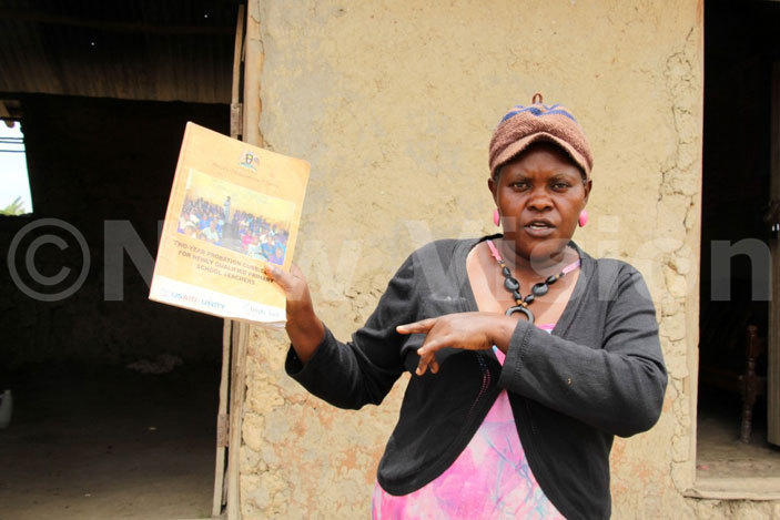 arriet amayengo the secretary for ducation ender and ealth displaying some of the government books in closed schools