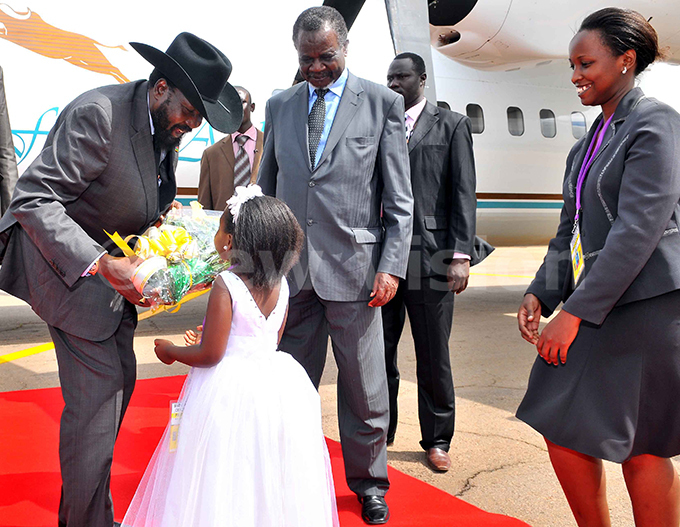 resident alva iir receives a bouquet of flowers from ochelle amugisha of ga han ursery school as  inister ggrey wori center and rotocal official ill uwagira right look on at ntebbe nternational airport on ay 11 2011 hoto by rthur intu