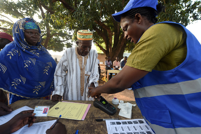 n official of the lectoral ommission  helps a voter to do biometric verification before casting his vote for the presidential election at ole district in northern hana on ecember 7 2016