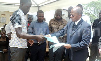 Muyingo awarding a bursary certificate to one of the students who are to study under bacef sponsorship 350x210