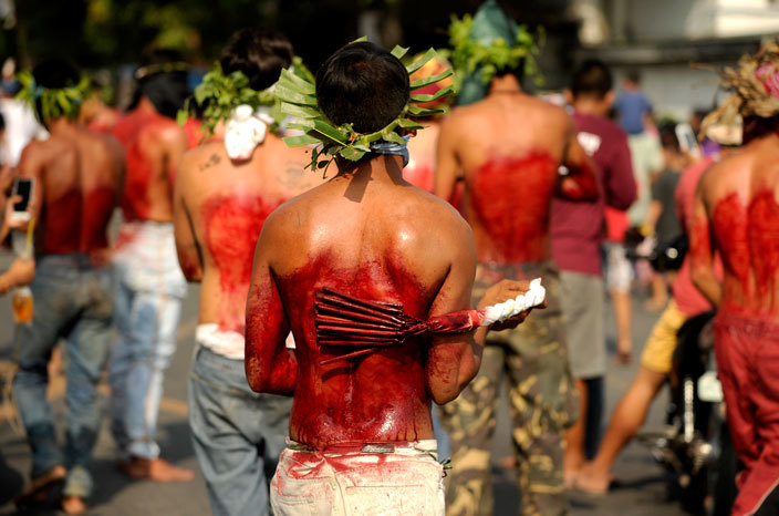 articipants whip their bloodied backs with bamboo as part of their penitence during the reenactment of the crucifixion of esus hrist for ood riday celebrations