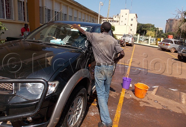 convict washing a magistrates vehicle at uganda oad ourt after the sentence