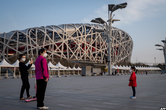 eople wearing facemasks outside the national irds est stadium back the site of the 2008 eijing lympics