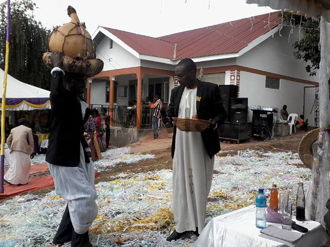 man carrying a gourd of a local brew which is a compulsory present to the brides father and his family