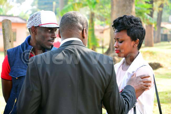 a sombrelooking ayondo is pictured standing outside court with a seemingly counseling lawyer aul enneth akande who has his hand consolingly placed on her shoulder as buga looks on with a near blush on his cheeks