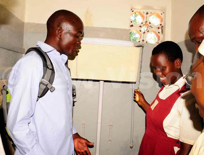ulius lobo the area manager rop in the ucket teaches a blind pupil how to use the newly installed waterborne toilets at adera chool for the lind hoto by ddie sejjoba