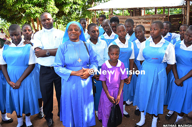 ubaga irls headteacher r lare akubulwa delivered her speech n her right is the schools chaplain r oses iyimba and in purple uniform is the headgirl of amuli nfant chool emimah amugabo