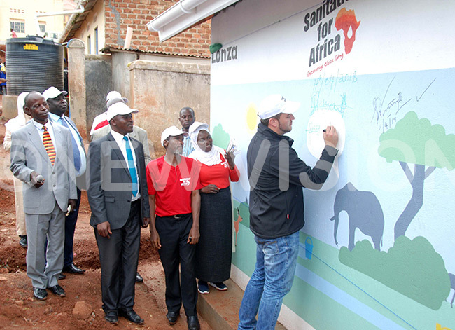 xpert manager onza outh frica uaan eyneka writes his remarks on walls of pit latrine as they officially hand it over to bdullahi un baas raning and ducation entre