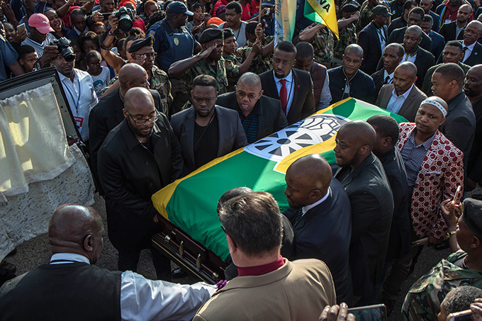 all bearers carry the casket of innie adikizelaandela covered with an  flag as remains of the the antiapartheid icon are returned to her home in oweto ohannesburg on pril 13 2018