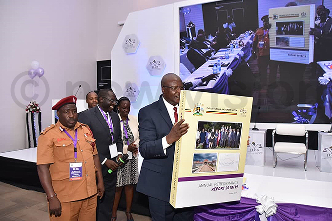 hief ustice art atureebe displays a copy of the 201819  annual performance report hoto by iriam amutebi