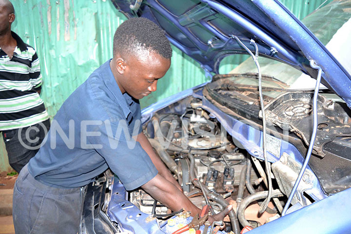 An expert trys to check what the problem in the car engine is